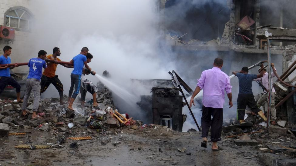 People try to extinguish fire at the site of a suicide car bombing outside the Yemeni President Abd-Rabbu Mansour Rabbu Hadi's residence in the southern city of Aden