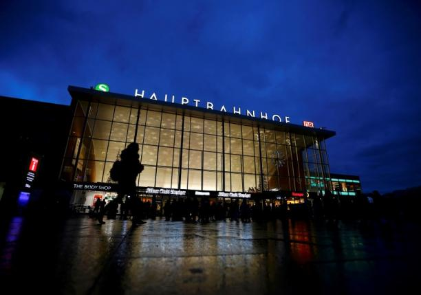 People are silhouetted as they walk past the main railway station in Cologne