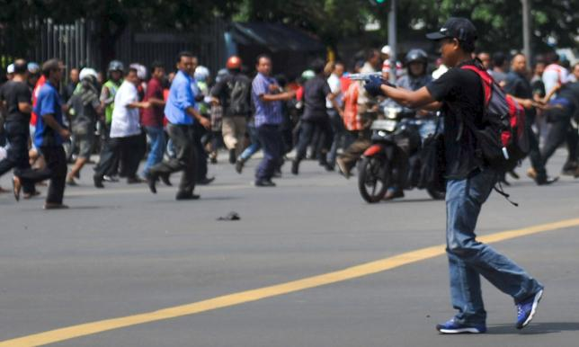 Man is seen holding a gun towards the crowd in central Jakarta