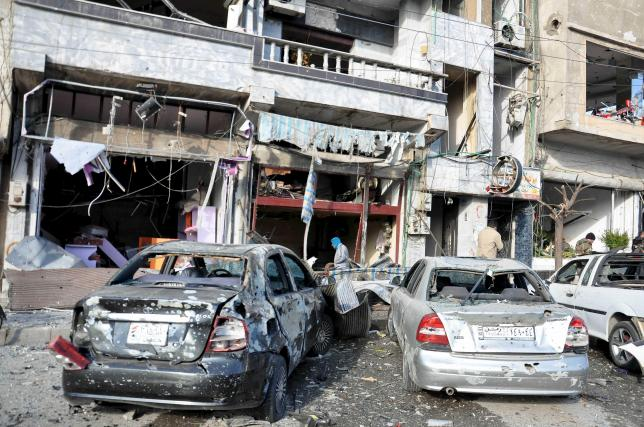 People inspect the site of a double bomb attack in the government-controlled city of Homs