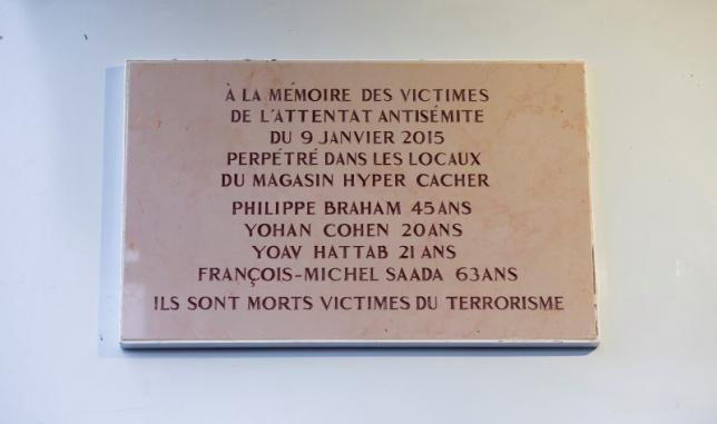 A view of the commemorative plaque unveiled by French President outside the Hypercacher kosher supermarket during a ceremony to pay tribute to the victims of last year's January attacks in Paris