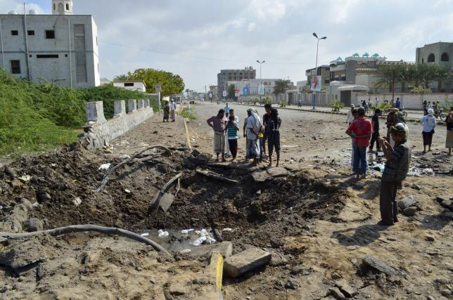 People gather around a crater caused by a Saudi-led air strike in Yemen's Red Sea port city of Houdieda