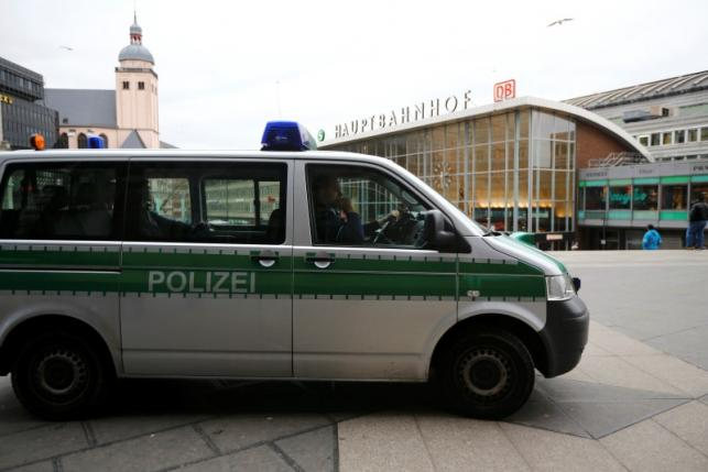 A police vehicle patrols at the main square and in front of the central railway station in Cologne