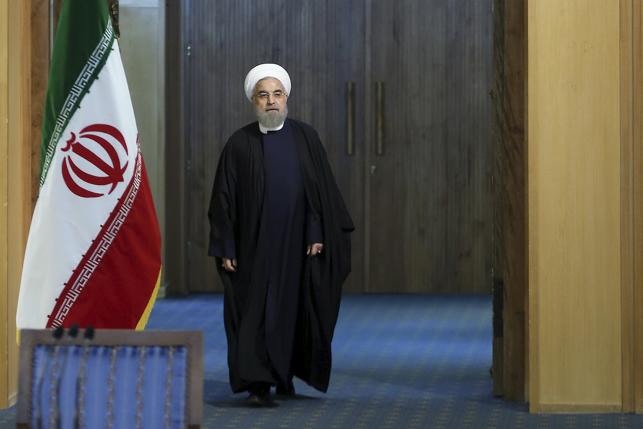 Iranian President Hassan Rouhani arrives for a news conference in Tehran