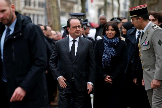 French President Hollande and Paris Mayor Hidalgo attend a ceremony to unveil a commemorative plaque at the site where policeman Ahmed Merabet was killed during the last year's January attack in Paris