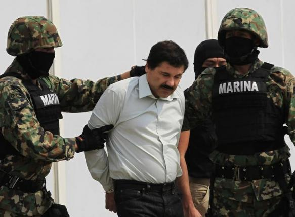 """Joaquin """"Shorty"""" Guzman (C) is escorted by soldiers during a presentation at the Navy's airstrip in Mexico City"""