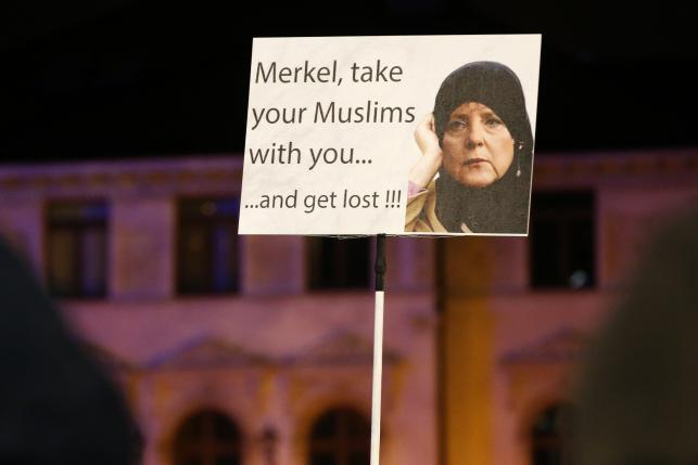 Members of LEGIDA, the Leipzig arm of the anti-Islam movement PEGIDA, hold a poster during a rally in Leipzig