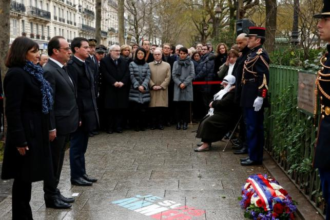 French President Francois Hollande, Paris Mayor Anne Hidalgo and Prime Minister Manuel Valls look at a commemorative plaque during a ceremony at the site where a policeman was killed during the last year's January attack in Paris