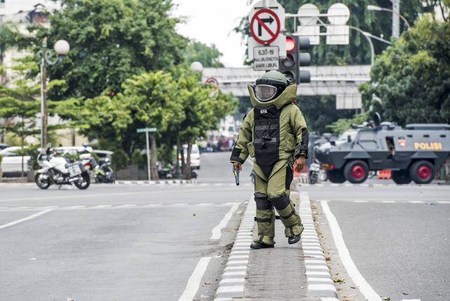 A member of the police bomb squad unit approaches the scene of an explosion following an attack on a police box in central Jakarta