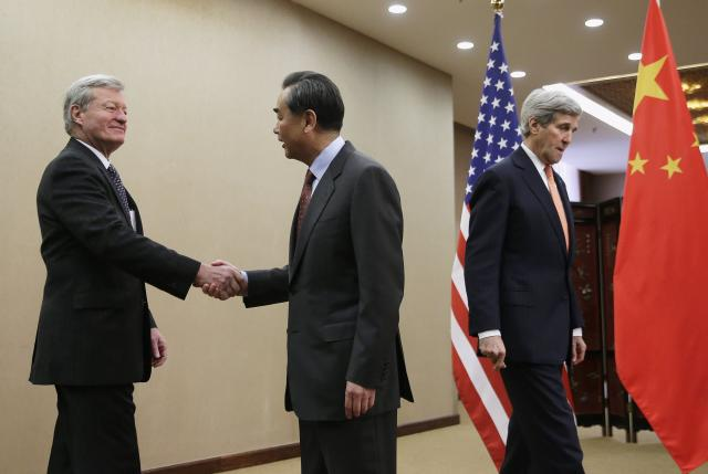 U.S. Secretary of State John Kerry walks past as Chinese Foreign Minister Wang Yi shakes hands with U.S. Ambassador to China Max Baucus before their bilateral meeting at the Ministry of Foreign Affairs in Beijing