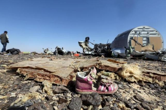 A child's shoe is seen in front of debris from a Russian airliner which crashed at the Hassana area in Arish city