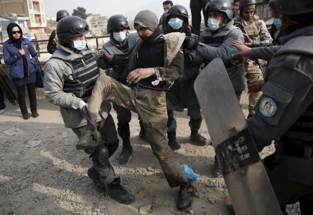 Police detain a man to be taken to a newly-opened treatment centre at Camp Phoenix, during a round up of suspected drug addicts in Kabul, Afghanistan