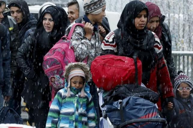 Migrants stand in queue before passing Austrian-German border