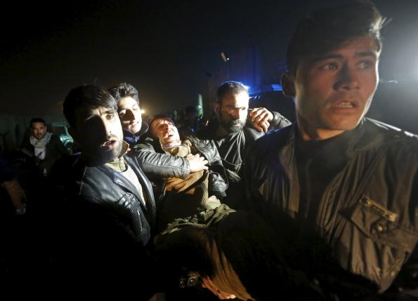 Afghan men carry a wounded man at the site of an explosion in Kabul, Afghanistan