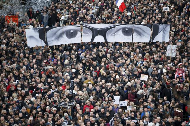 File picture of people holding panels to create an image depicting the eyes of Charb at a solidarity march in the streets of Paris