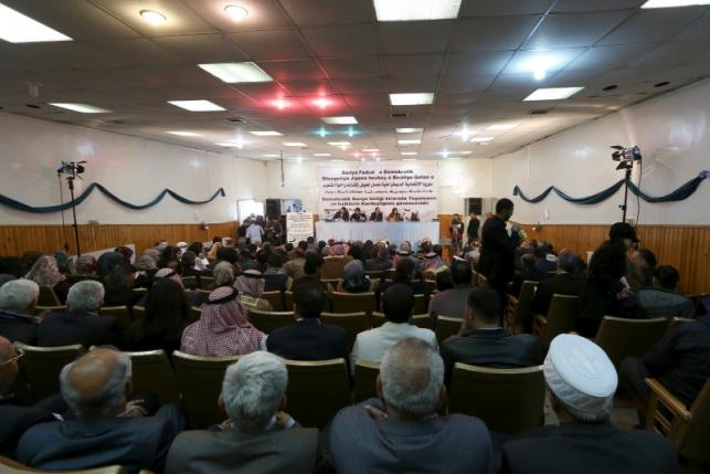 "Bureau members of a preparatory conference to announce a federal system discuss a ""Democratic Federal System for Rojava - Northern Syria"" in the Kurdish-controlled town of Rmeilan, Hasaka province"