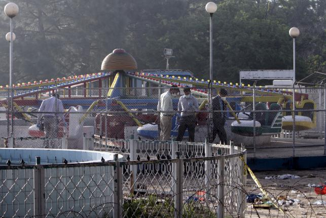 Forensic officers look for evidence at the site of a blast that happened outside a public park on Sunday, in Lahore