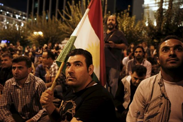 File photo of a pro-Kurdish demonstrator holding a flag of Syrian Kurdish Democratic Union party during a rally in Athens