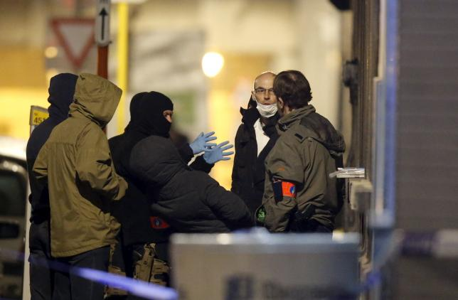 Masked Belgian police secure the entrance to a building in Schaerbeek