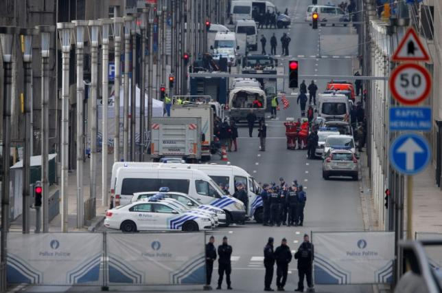Belgian police and emergency personnel secure the Rue de la Loi following an explosion in Maalbeek metro station in Brussels