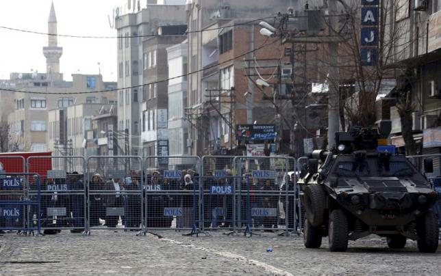 File photo of people standing behind the security barriers in the Kurdish-dominated southeastern city of Diyarbakir