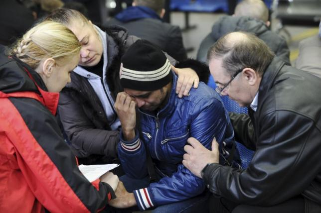 A psychologist of the Russian Emergencies Ministry speaks with a relative of a victim of the crashed Flydubai Boeing 737-800 at the airport of Rostov-On-Don, Russia