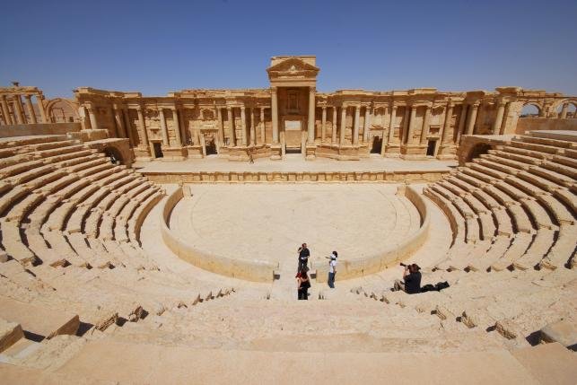 File photo of tourists taking pictures at the ancient Palmyra theater in the historical city of Palmyra