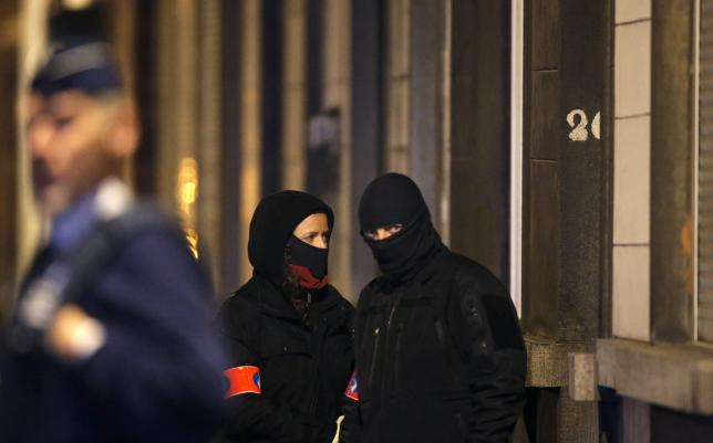 Masked Belgian police secure the entrance to a building in Schaerbeek during police operations  in Brussels