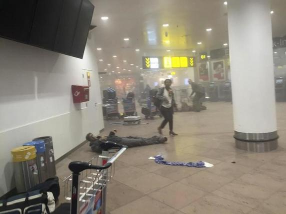 An injured man lies at the scene of explosions at Zaventem airport near Brussels