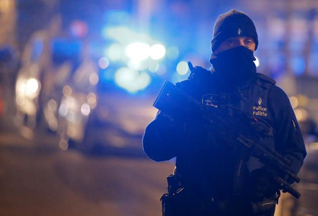 A masked Belgian police officer takes part in police operations in Schaerbeek