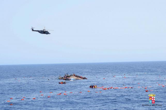 "Migrants from a capsized boat are rescued during a rescue operation by Italian navy ships ""Bettica"" and ""Bergamini"" off the coast of Libya"