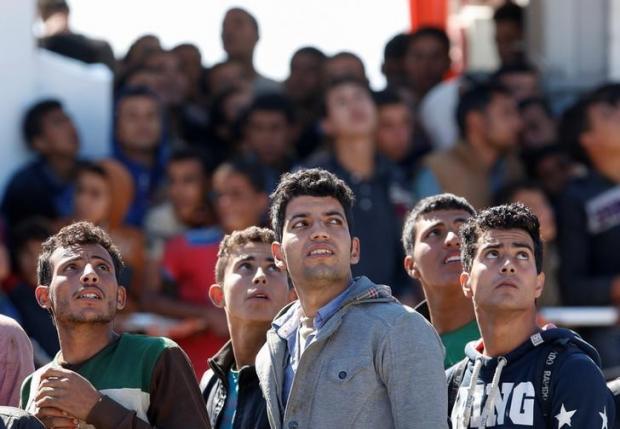 Migrants disembark from the Italian coastguard vessel Peluso in the Sicilian harbour of Augusta