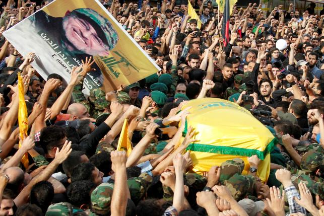 Hezbollah members carry the coffin and a picture of top Hezbollah commander Mustafa Badreddine, who was killed in an attack in Syria, during his funeral in Beirut's southern suburbs