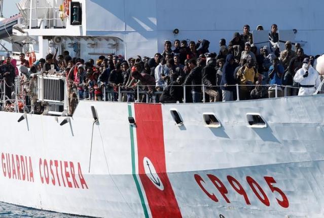 Migrants arrive by the Italian coastguard vessel Peluso in the Sicilian harbour of Augusta
