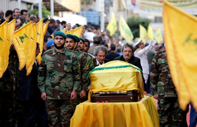 Brothers of top Hezbollah commander Mustafa Badreddine, who was killed in an attack in Syria, mourn over his coffin during his funeral in Beirut's southern suburbs