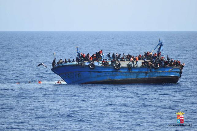 "Migrants are seen on a capsizing boat before a rescue operation by Italian navy ships ""Bettica"" and ""Bergamini"" (unseen) off the coast of Libya"