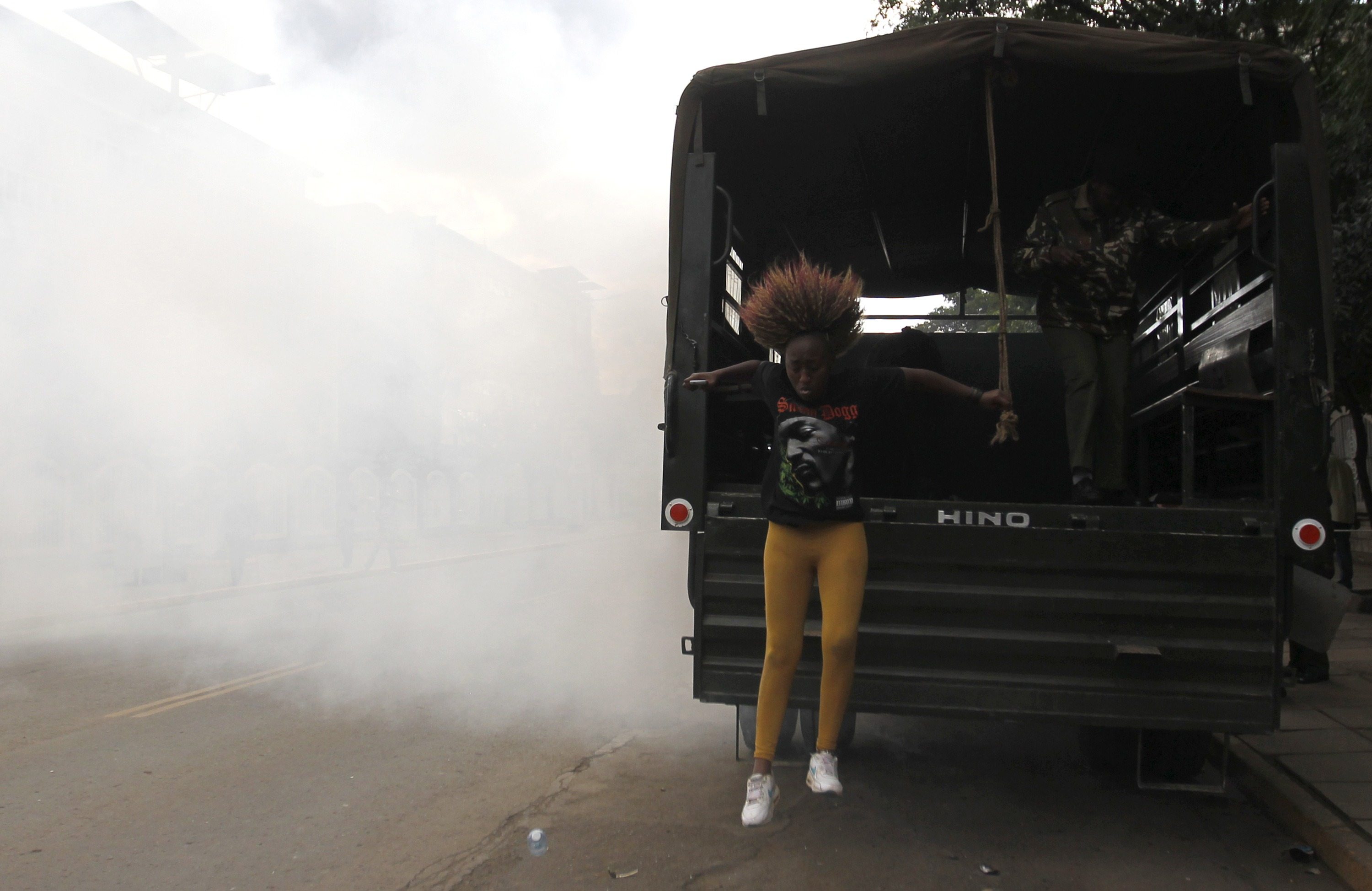 A detained protester jumps from a police truck as she escapes after riot police released teargas to disperse the #OccupyHarambeeAve demonstration in Nairobi