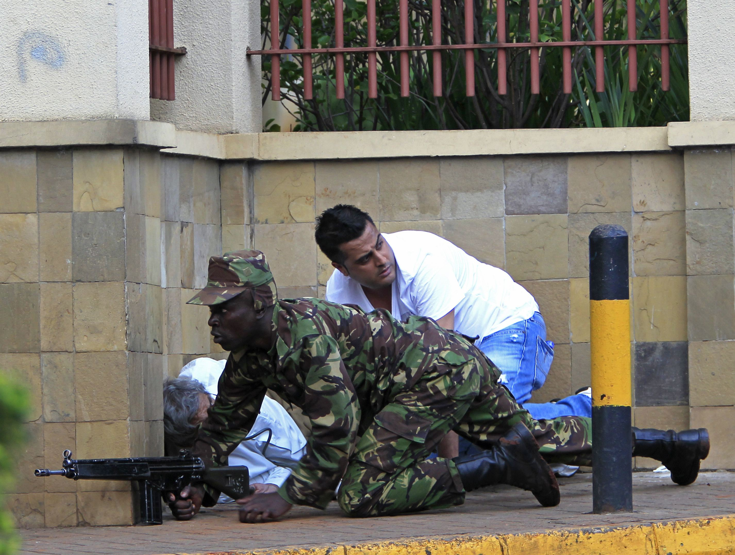 A Kenyan army soldier takes cover behind a wall at Westgate Shopping Centre in Nairobi