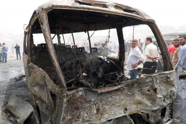 People inspect the site of car bomb attack in Baghdad al-Jadeeda