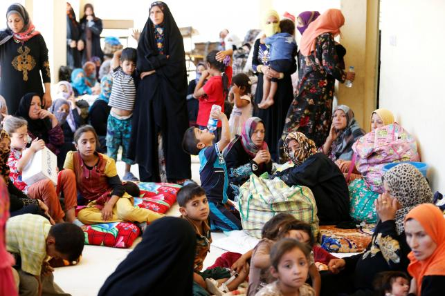 Civilians who fled their homes due to clashes on the outskirts of Falluja, gather in the town of Garma