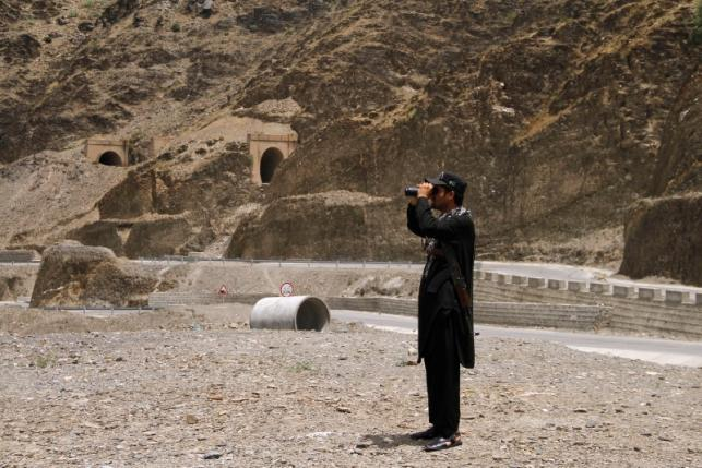 A member of Pakistan's Frontier Corps uses binoculars to survery the border region outside Torkham