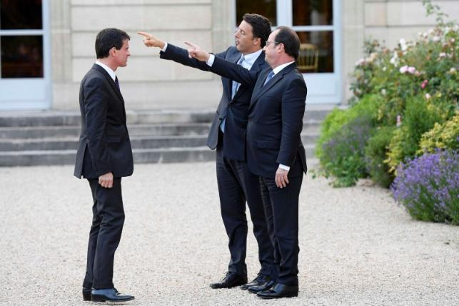 French Prime Minister Manuel Valls looks at French President Francois Hollande and Italy's Prime Minister Matteo Renzi point as they visit the gardens at the Elysee Palace in Paris