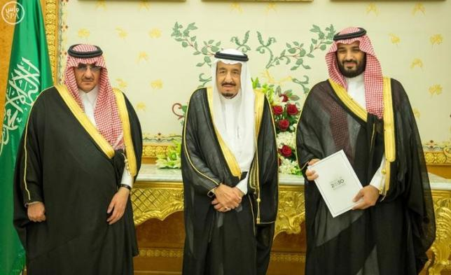 Saudi Crown Prince Mohammed bin Nayef, Saudi King Salman, and Saudi Arabia's Deputy Crown Prince Mohammed bin Salman stand together as Saudi Arabia's cabinet agrees to implement a broad reform plan known as Vision 2030 in Riyadh,