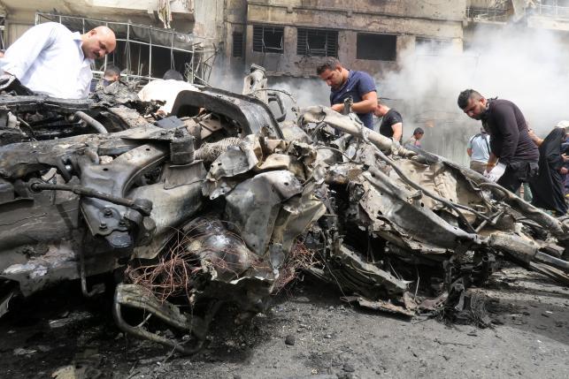 People gather at the site of car bomb attack in Baghdad al-Jadeeda