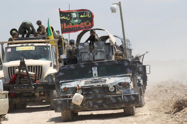 Iraqi security forces and Shi'ite fighters sit in military vehicles near Falluja