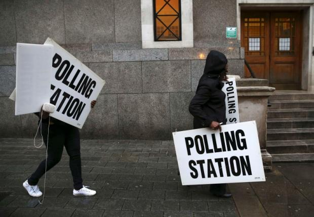 Electoral workers carry signs as they prepare a polling station for the Referendum on the European Union in north London