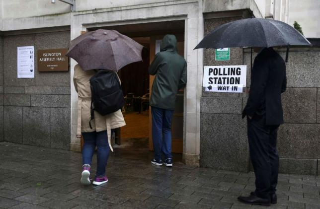 People queue in the rain outside a polling station for the Referendum on the European Union in north London, Britain