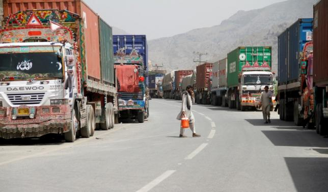 Transit trucks stranded due to the border skirmishes between Pakistan and Afghanistan are parked on the side of the road leading to the border in Torkham