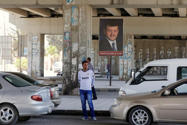 People walk past a poster of Jordan's King Abdullah near the General Intelligence directorate offices near al Baqaa Refugee Camp