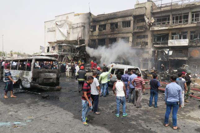 People gather at the site of car bomb attack in Baghdad al-Jadeeda